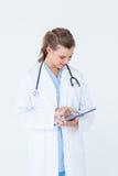 指向片剂个人计算机的微笑的医生 免版税图库摄影