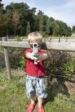 指向玩具的小男孩佩带的太阳镜开枪 免版税库存图片