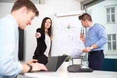 指向男性同事的女实业家使用膝上型计算机 免版税库存照片