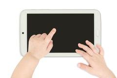 指向白色片剂计算机的婴孩手 库存图片
