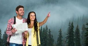 指向的妇女,当拿着地图的人在旅行在有雾的天气时的山期间 免版税库存照片