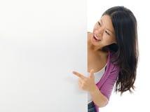 指向空白的广告牌的亚裔妇女。 库存照片