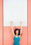 指向空白的海报的愉快的妇女 库存图片