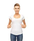 指向空白的白色T恤杉的微笑的妇女 图库摄影