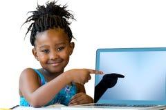 指向空白的膝上型计算机屏幕的小非洲女孩 免版税图库摄影