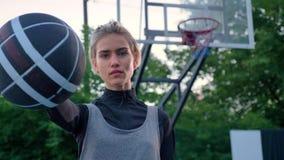 指向篮球的美丽的白肤金发的妇女入照相机,站立在公园在白天期间,箍的专业球员  股票录像