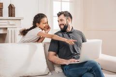 指向膝上型计算机屏幕的女孩,当父亲坐沙发时 免版税图库摄影