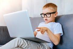 指向膝上型计算机屏幕的逗人喜爱的白肤金发的男孩 库存照片