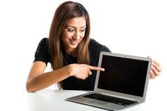指向膝上型计算机的可爱的年轻亚裔印地安少年妇女 免版税库存照片
