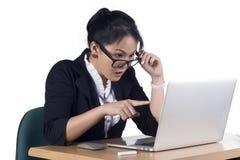 指向膝上型计算机的屏幕的女商人看起来冲击和s 免版税库存图片