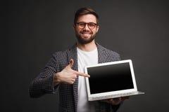 指向膝上型计算机的微笑的人 库存照片