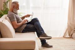 指向膝上型计算机的有胡子的人,当在家时坐沙发 图库摄影