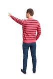 指向衬衣和牛仔裤的年轻人后面看法 库存图片