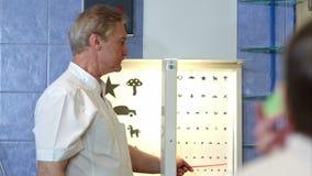 指向视力检查表信件的年长男性眼科医生  股票录像