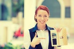指向许多信用卡的微笑的女商人在她的钱包里 免版税库存图片