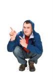 指向蹲的手指愉快的人 库存照片