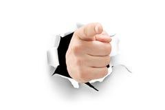 指向通过在纸的一个孔的一只男性手的看法 库存照片
