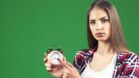 指向闹钟的美丽的少妇看起来严肃 股票视频
