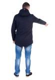 指向附头巾皮外衣的年轻人后面看法  免版税库存图片