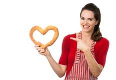 指向面包爱重点的美丽的妇女。 免版税图库摄影