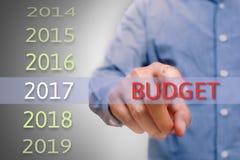 指向预算文本的Bussinessman手在2017年 瞄准概念 免版税库存图片