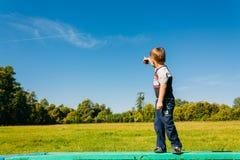 指向飞行飞机的小男孩在蓝色夏天 免版税库存图片