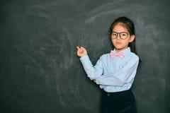指向黑板的恼怒的相当小老师 免版税库存图片
