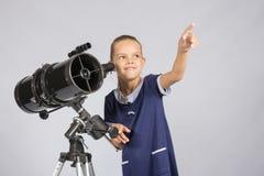 指向满天星斗的天空的年轻天文学家 免版税库存照片