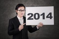 指向2014年广告牌的商人 免版税库存图片