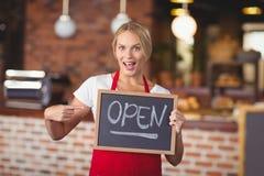 指向黑板开放标志的俏丽的女服务员 免版税库存照片