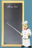 指向黑板菜单的厨师 库存照片