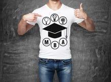 指向他的手指的一个人的特写镜头与毕业帽子的剪影的胸口 免版税图库摄影