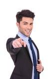 指向他的手指的微笑的商人 免版税库存图片