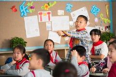 指向他的手指的男小学生在中国学校 免版税图库摄影