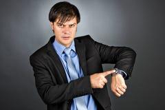 指向他的有一个恼怒的表示的手表的年轻商人 库存图片