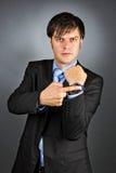 指向他的有一个恼怒的表示的手表的年轻商人 库存照片