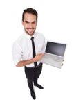 指向他的膝上型计算机的微笑的商人 免版税库存照片