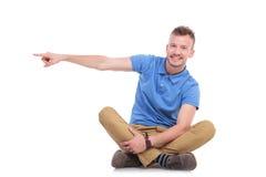 指向他的边的安装的年轻偶然人 免版税图库摄影