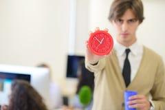 指向他的年轻恼怒的商人手表作为概念迟到工作 图库摄影