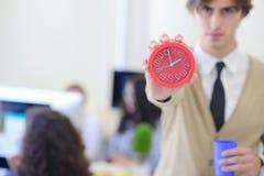 指向他的年轻恼怒的商人手表作为概念迟到工作 免版税库存照片