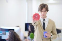 指向他的年轻恼怒的商人手表作为概念迟到工作 免版税库存图片