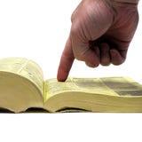 指向黄页书的手的手指 免版税库存图片