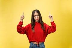 指向copyspace的年轻美丽的亚裔妇女,在黄色背景 免版税库存图片