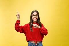 指向copyspace的年轻美丽的亚裔妇女,在黄色背景 免版税库存照片