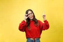 指向copyspace的年轻美丽的亚裔妇女,在黄色背景 图库摄影
