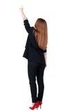 指向wal的后面观点的年轻红头发人女商人 免版税图库摄影