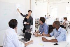 指向whiteboard的妇女在一次会议上在一个繁忙的办公室 免版税图库摄影