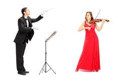 指挥一把女性使用的小提琴的公管弦乐队指挥 库存图片