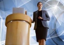 指挥台的女实业家发言在会议上与未来派形状 免版税库存图片