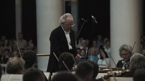 指挥小提琴乐队的白发指挥在经典样式音乐厅里 影视素材
